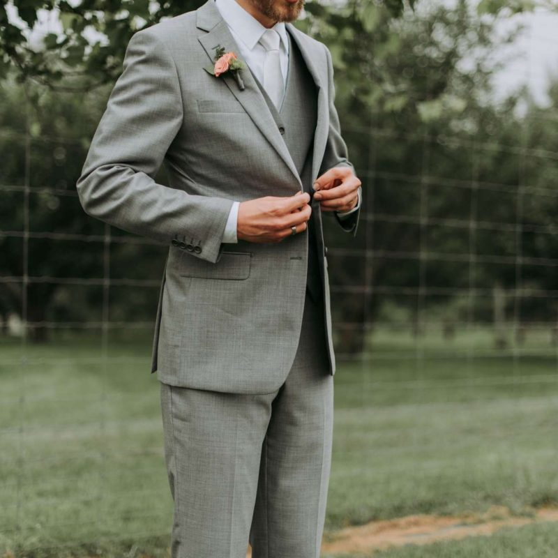 man buttoning tuxedo jacket