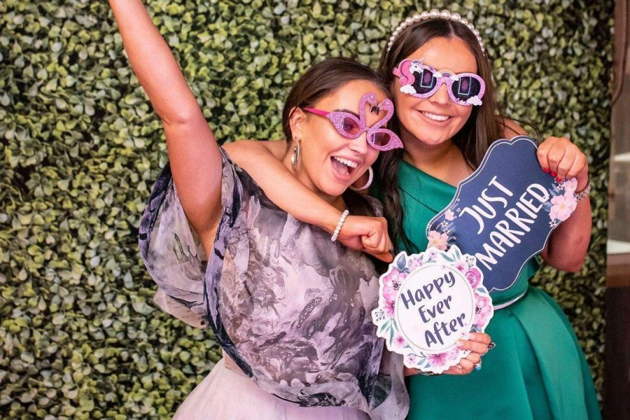 wedding guests hold props for photo