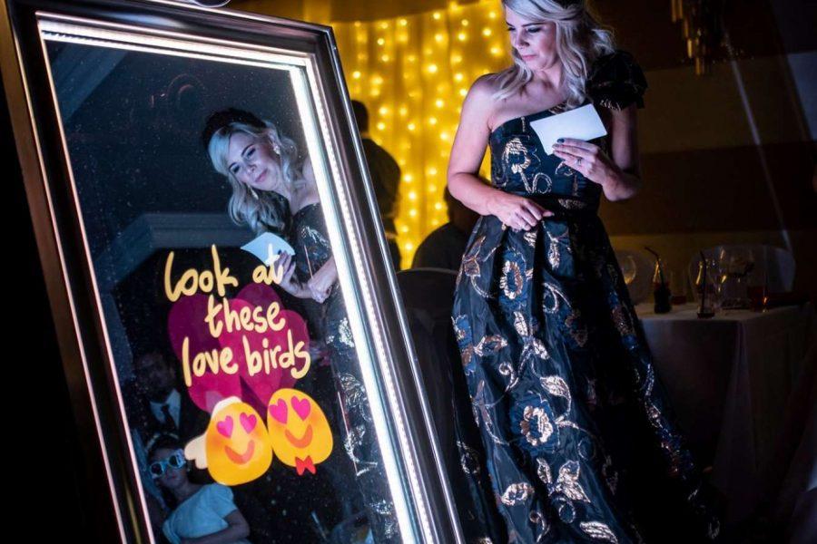 woman standing near wedding photo mirror