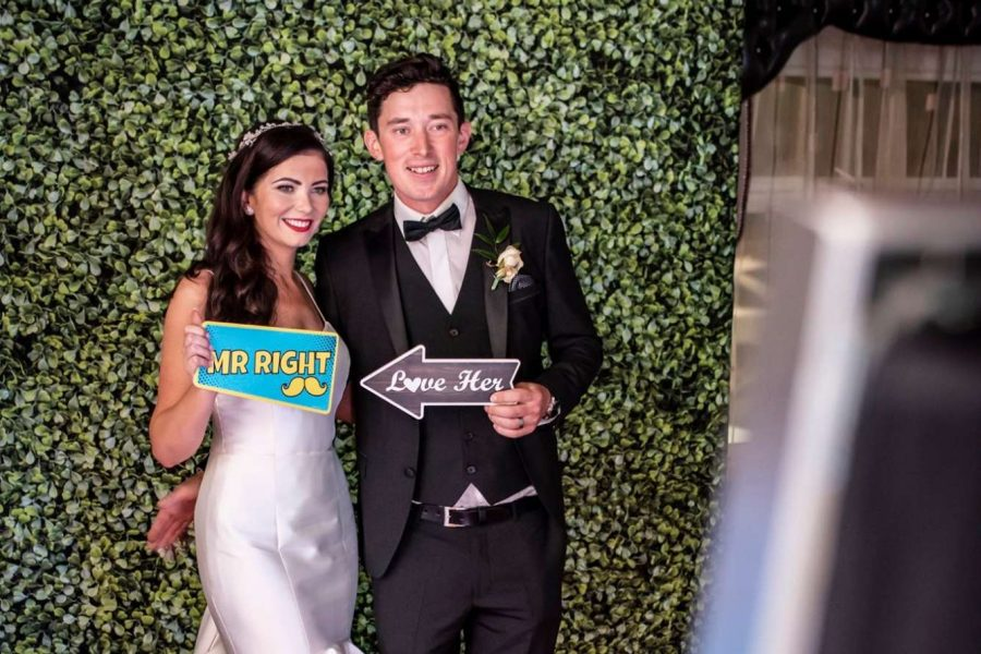 bride and groom taking selfie on mirror photo booth