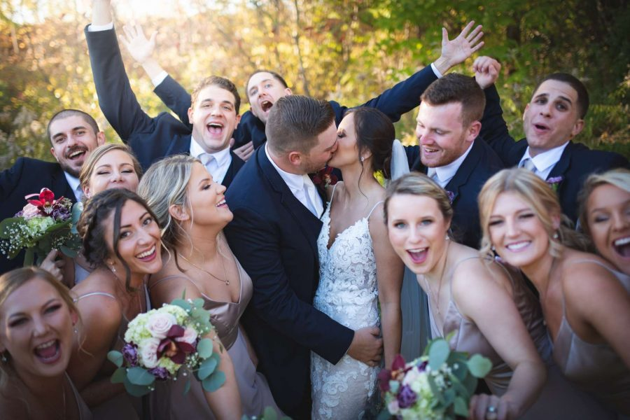 bride and groom kiss while bridal party celebrates
