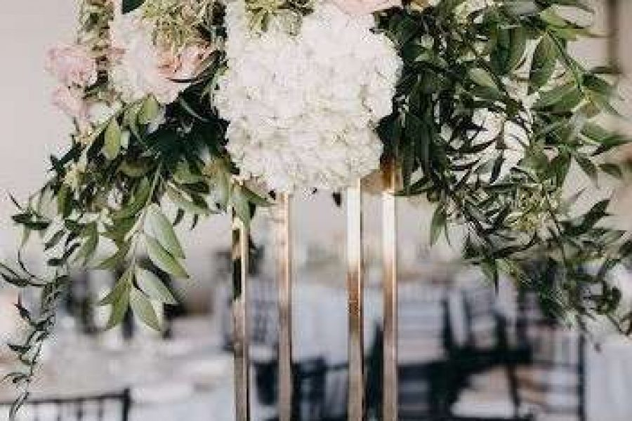 Tall wedding centerpiece with flowers and leaves
