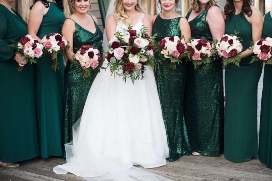 Bridal party holds bouquets of assorted flowers