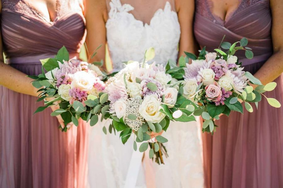 bride and bridesmaids hold wedding flowers