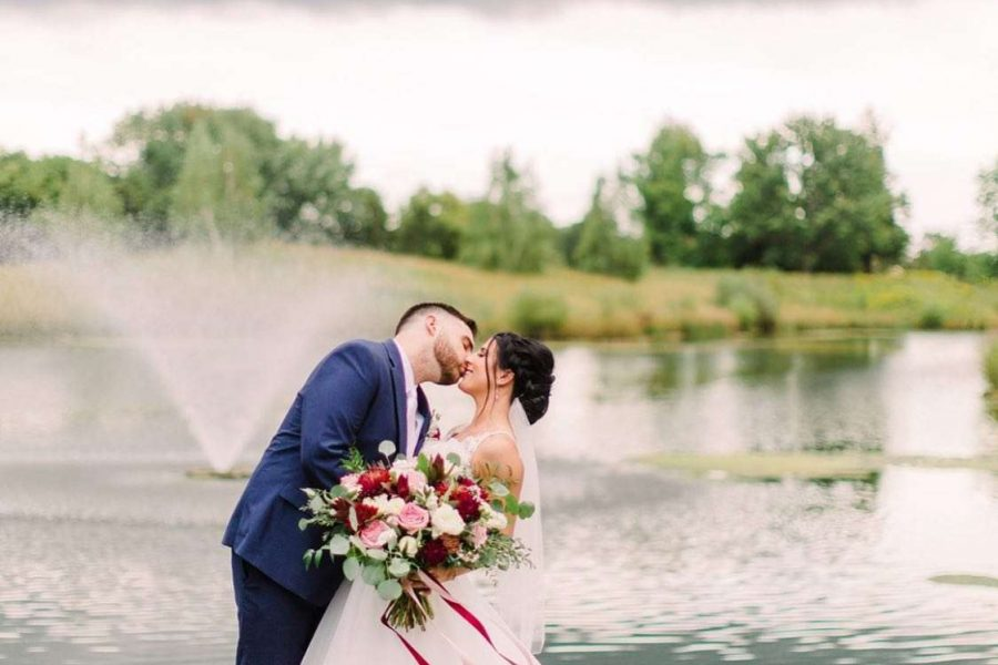 Couple kiss and bride holds large bouquet of flowers