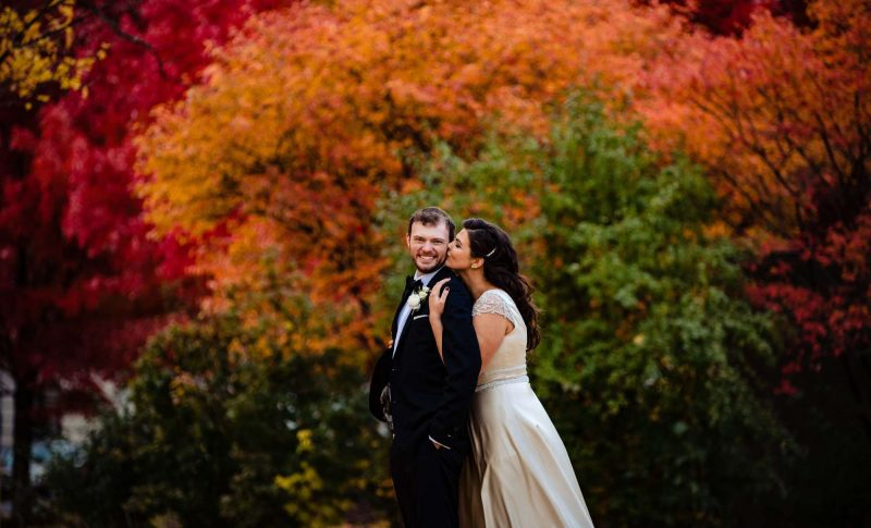 bride kisses groom by fall trees in Syracuse, NY