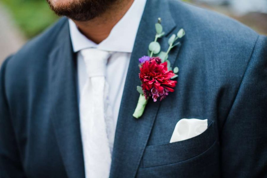 groom wears small wedding flowers