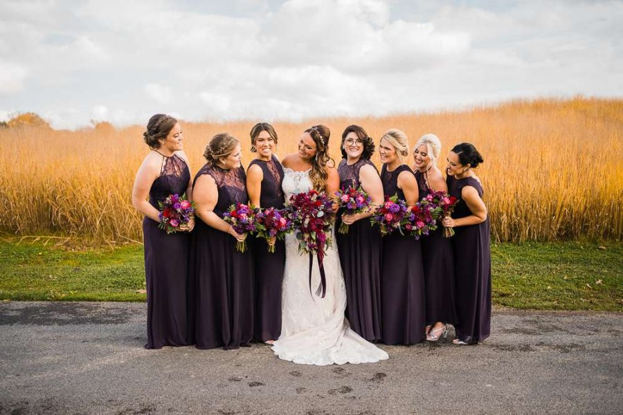 Bride and bridesmaids hold bouquets of red and purple flowers