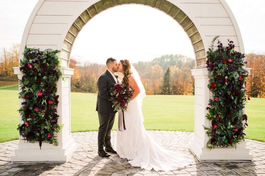 Couple kiss under arch decorated with flowers